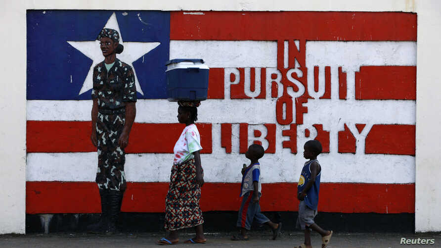 A woman and two children walk past a mural in Monrovia November 10, 2011.