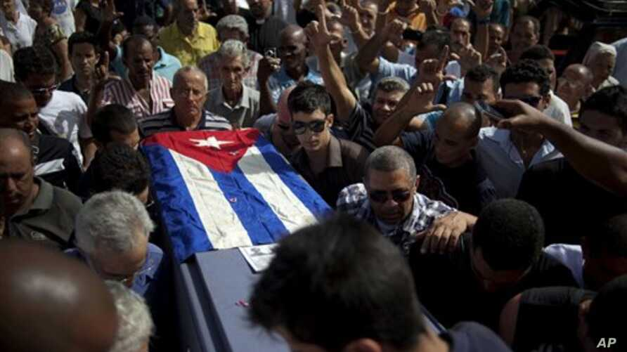 Friends and family of the late Cuban activist Oswaldo Paya carry his flag draped coffin during his burial at a cemetery in Havana, Cuba, July 24, 2012.