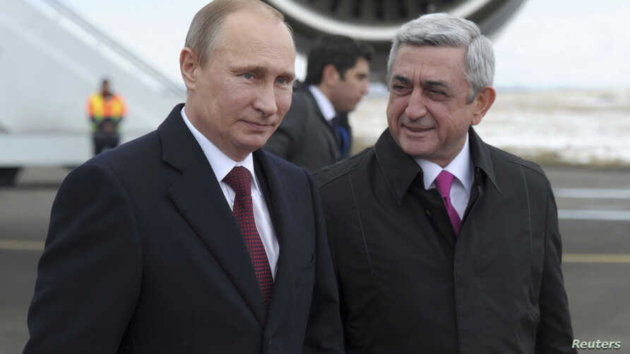 Russian President Vladimir Putin (L) walks with Armenian President Serge Sarksyan after arriving in the Armenian city of Gyumri, Dec. 2, 2013.