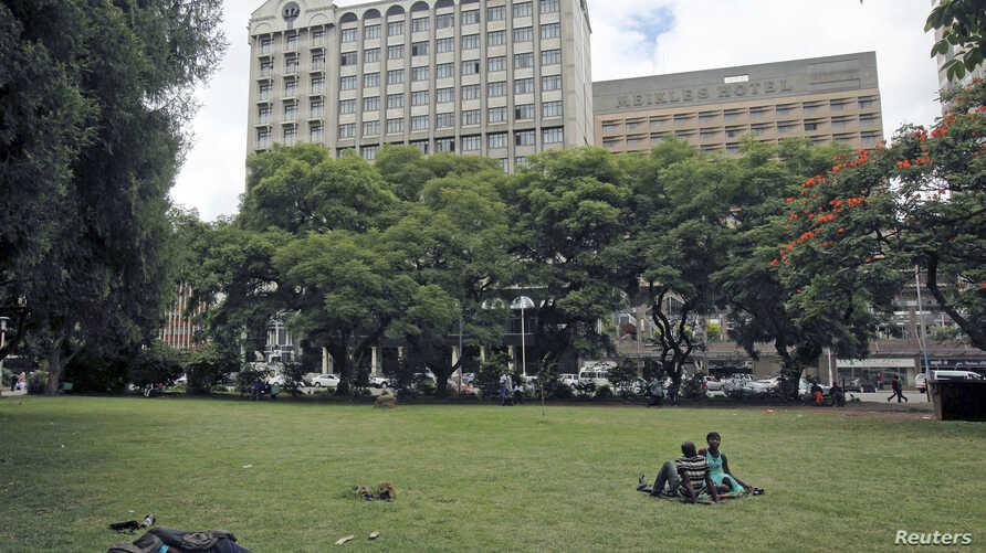 Zimbabweans rest at a park outside Meikles Hotel in central in Harare, February 24, 2015.