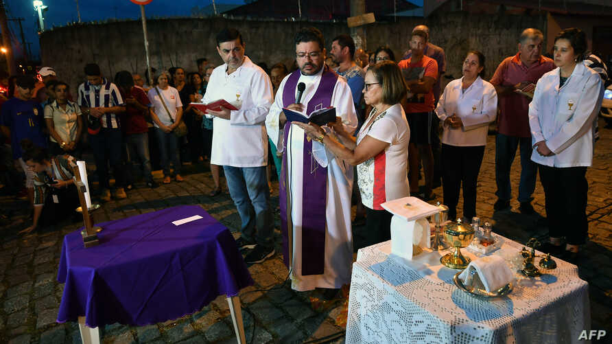 A priest gives mass nearby the Raul Brasil public school, following a shooting in which ten people -including the two shooters- died and 15 resulted injured, in Suzano, Sao Paulo metropolitan region, Brazil, on March 13, 2019.