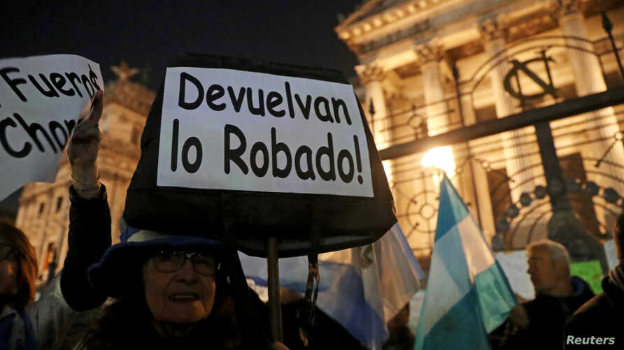 """A woman holds up a sign that reads """"give back what was stolen"""" during a demonstration against corruption and to demand the Senate strip former Argentine president and senator Cristina Fernandez de Kirchner of immunity, in Buenos Aires, Argentina, Aug"""