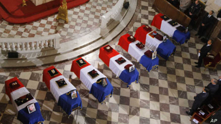 French President Nicolas Sarkozy, stood right of flag-draped coffins inside the Invalides church as tribute is paid by France to the seven French soldiers killed last week in Afghanistan during a national ceremony in Paris, July 19, 2011