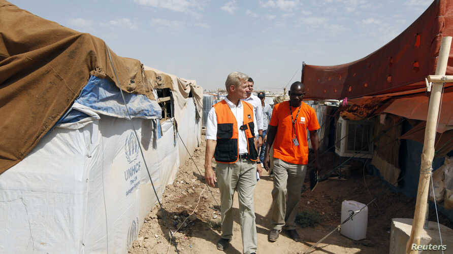 FILE - The secretary-general of the Norwegian Refugee Council (NRC), Jan Egeland (front) visits Domiz camp in the northern Iraqi province of Dohuk, Aug. 21, 2013.
