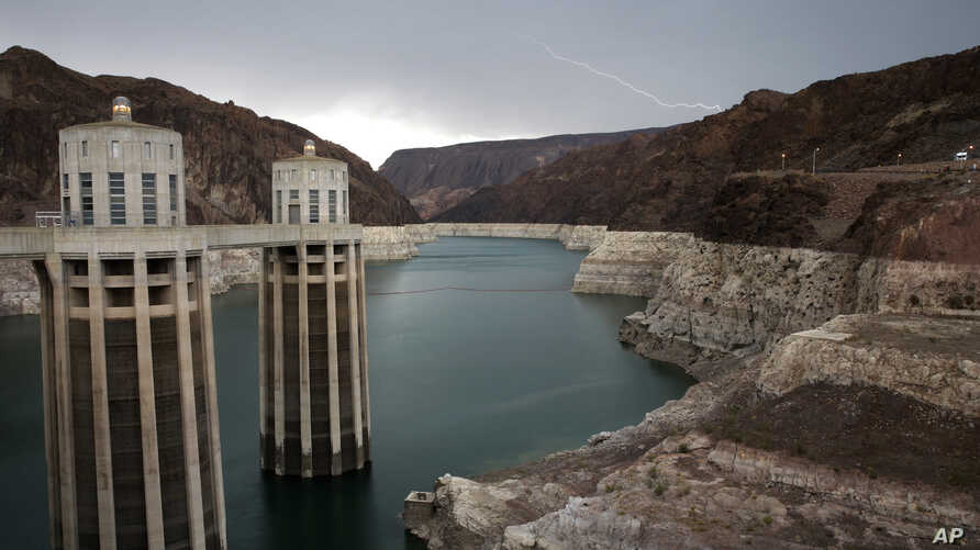 FILE - In this July 28, 2014, photo, lightning strikes over Lake Mead near Hoover Dam at the Lake Mead National Recreation Area in Arizona. For  Arizona and Nevada, the reservoir on the Colorado River is a major source of drinking water.