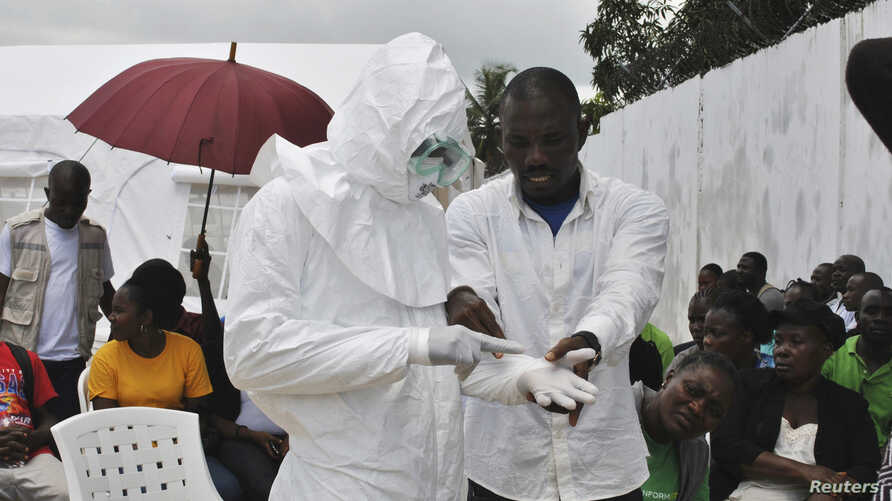 A volunteer health worker practices using a personal protective equipment (PPE) suit at a newly-constructed Ebola virus treatment centre in Monrovia, Liberia, Sept. 21, 2014.