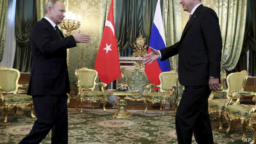 Russia's President Vladimir Putin, left, walks to shake hands with Turkey's President Recep Tayyip Erdogan, right, as he welcomes him prior to their meeting in Moscow, Russia, Monday, April 8, 2019.