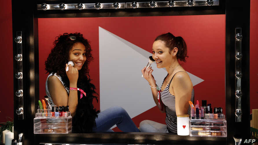 "FILE - Girls look in a mirror as they put makeup on during a beauty and fashion fair inspired by the US ""Beautycon"" event, a  gathering of fashion bloggers and YouTube personalities, May 28, 2016, in Paris. Researchers found that in most of the world"