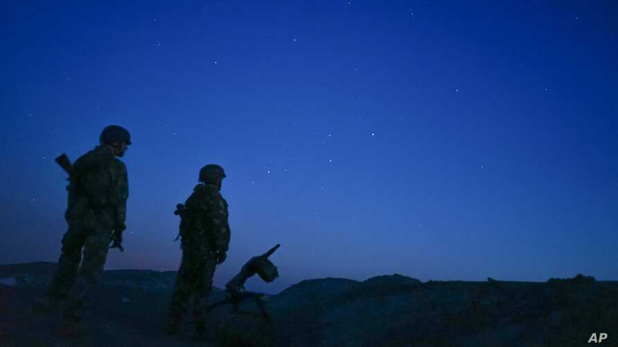 FILE - Russia-backed rebels are seen guarding territory after sunset near Donetsk, eastern Ukraine, Aug. 2, 2015.