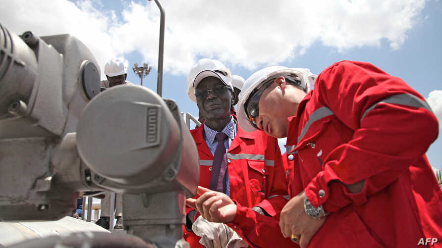 South Sudan's Minister for Petroleum and Mining Stephen Dhieu Dau (L) prepares to press button to resume oil production May 5, 2013, Paloch, South Sudan