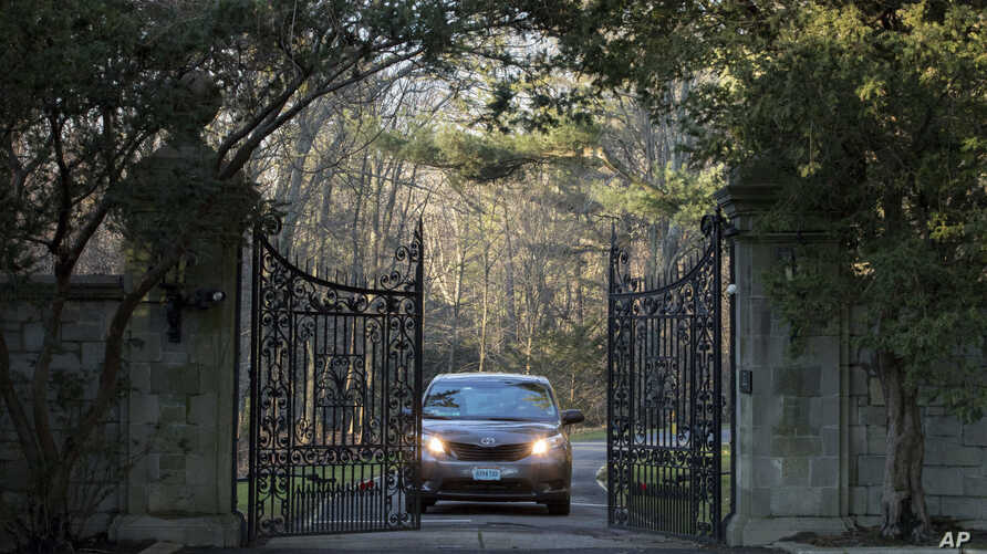 FILE - A car with diplomatic license plates drives out of a compound near Glen Cove, N.Y., on Long Island, Dec. 30, 2016.