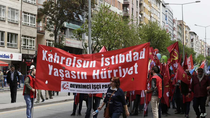 Protesters hold banners during a May day protest in Ankara, Turkey , May 1, 2017. Workers and activists marked May Day with defiant rallies and marches for better pay and working conditions Monday.