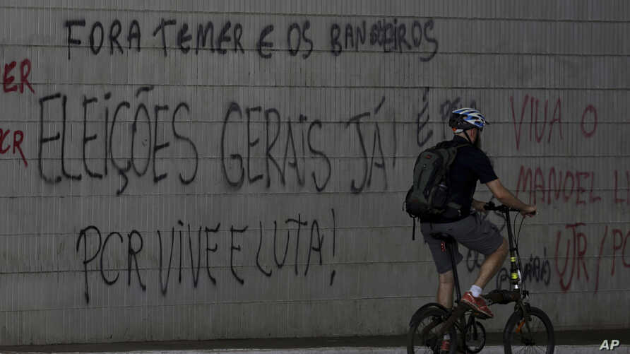 """A cyclist passes graffiti that reads in Portuguese """"Get out Temer and bankers. General elections now!"""" at a traffic light at the bus station in Brasilia, Brazil June 12, 2017."""