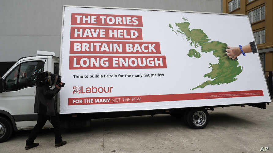 FILE - A cameraman films a poster being unveiled by Britain's opposition Labor party for the upcoming general election, in London, May 11, 2017.