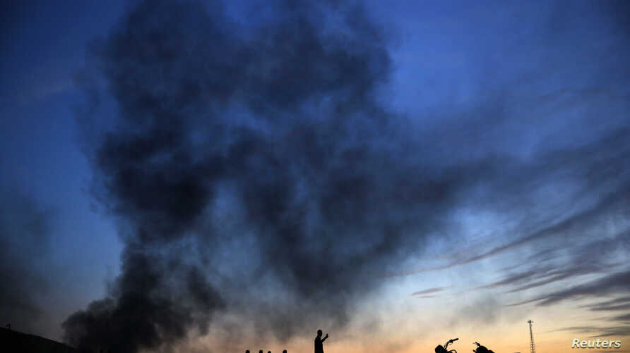 Kurdish refugees stand and walk on a hilltop as thick smoke rises from the Syrian town of Kobani during heavy fighting between Islamic State and Kurdish Peshmerga forces, seen from near the Mursitpinar border crossing on the Turkish-Syrian border in