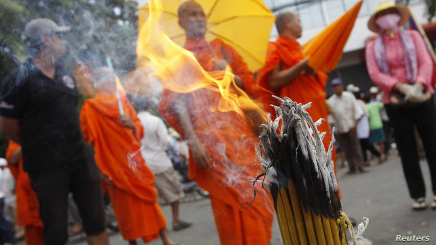 Buddhist monks and other protesters are seen gathered near the Vietnamese embassy during a protest in Phnom Penh August 13, 2014.