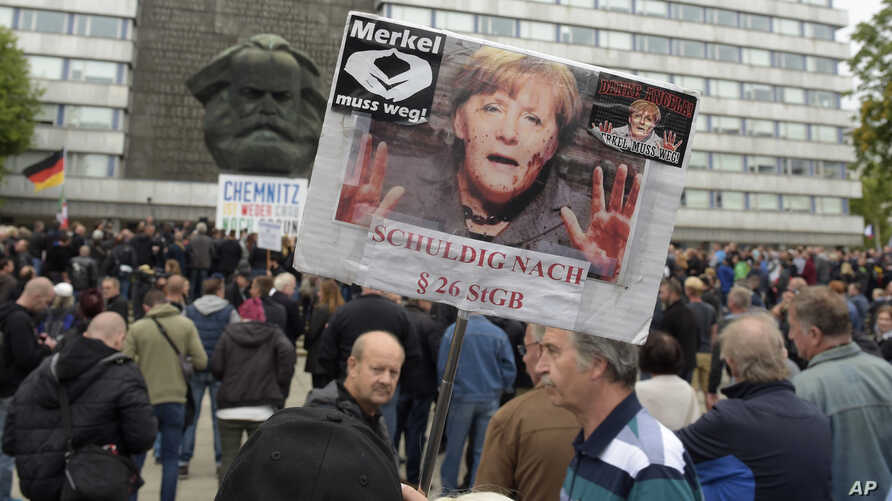 "A protester holds a poster with a photo of Angela Merkel reading ""Merkel must go"" and implying she is guilty of incitement in Chemnitz, eastern Germany, Sept. 1, 2018, after several nationalist groups called for marches protesting the recent killing"