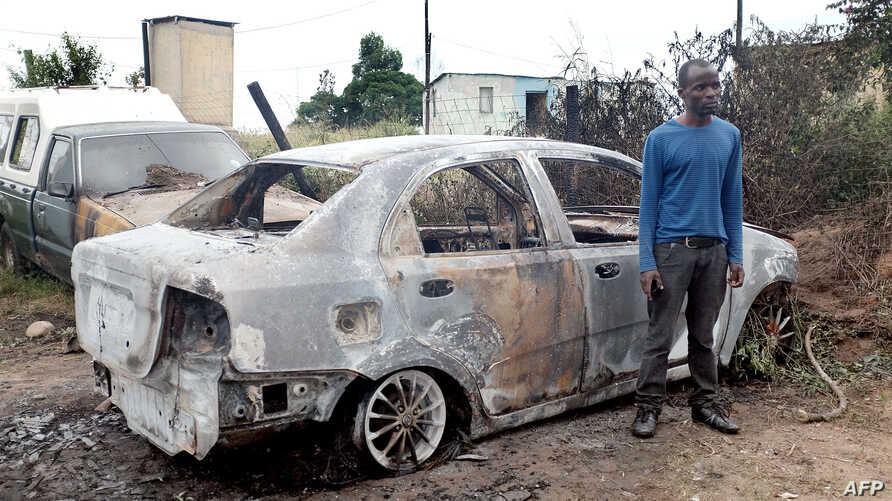 A foreign national from Zimbabwe stands by one of his two cars set alight after he survived a petrol bomb attack at his home in Illovo, some 55 kilometers south of Durban, South Africa, April 19, 2015
