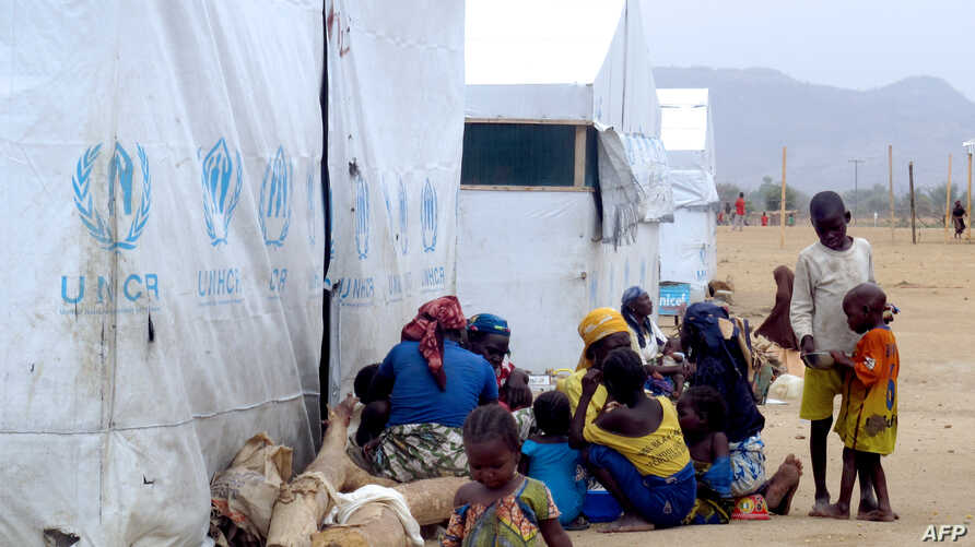 FILE - Nigerian refugees sit by a UNHCR tent in the refugee camp of Minawao, on the border of Nigeria at the extreme north of Cameroon, March 29, 2014.