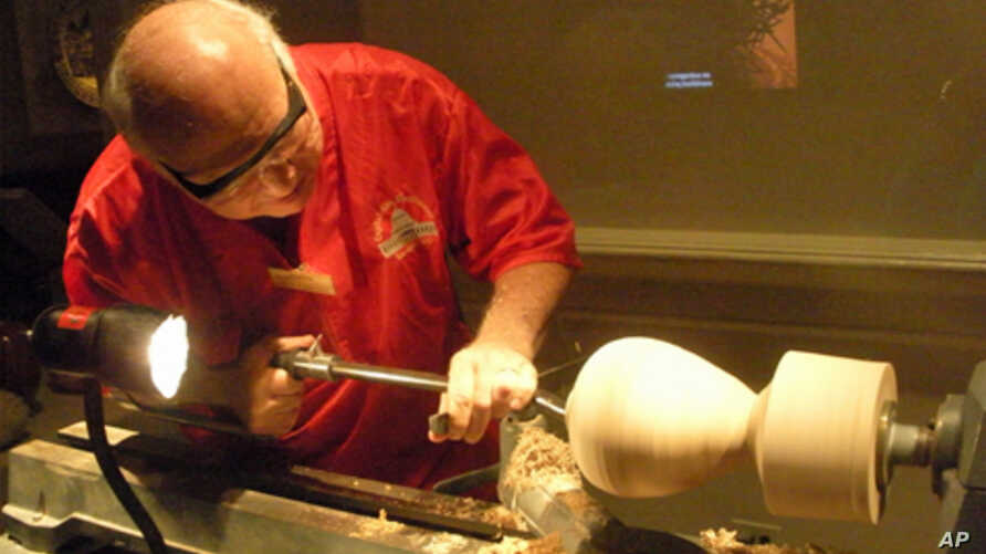 Wood turner Eliot Feldman uses a lathe to shape a block of wood into a drinking vessel.