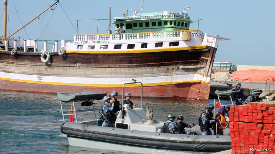 Chinese navy officers dock on the shores of the Gulf of Aden to hand over three suspected pirates involved in the attempted hijacking in April of the OS35, a cargo ship.
