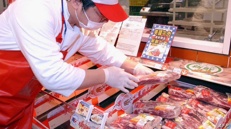 A staff member at a Taipei hyper market examines imported US beef, (File Photo).