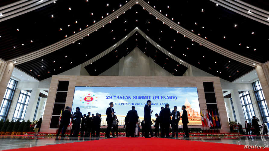 Delegates stand outside the plenary session at the ASEAN Summit in Vientiane, Laos, Sept. 6, 2016.