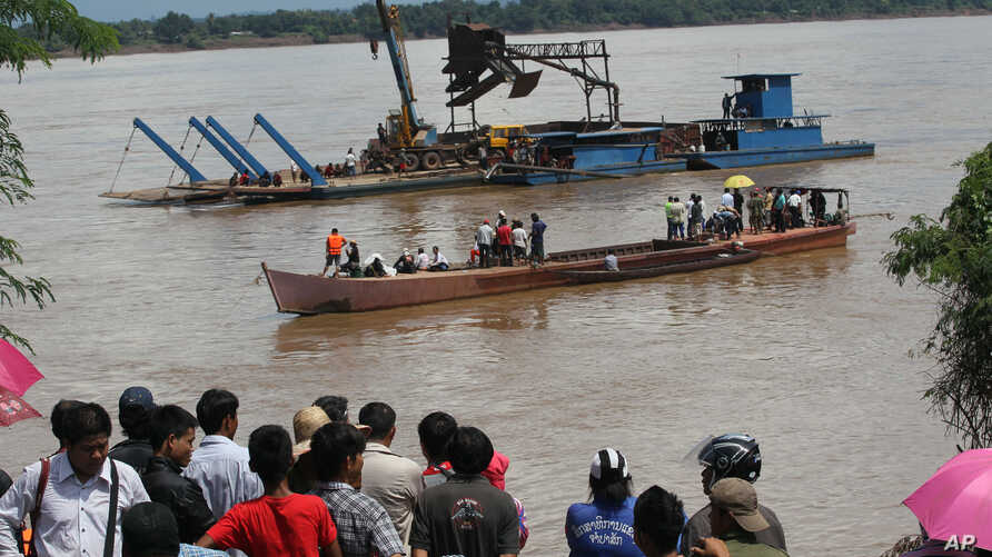 Onlookers watch the search operation for the lost Lao Airlines plane on the banks of the Mekong River in Pakse, Laos, Oct. 17, 2013.