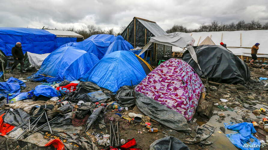 Migrants walk among tents in a muddy field at a camp of makeshift shelters for migrants and asylum-seekers from Iraq, Kurdistan, Iran and Syria, called the Grande Synthe jungle, near Calais, France, Feb. 3, 2016.