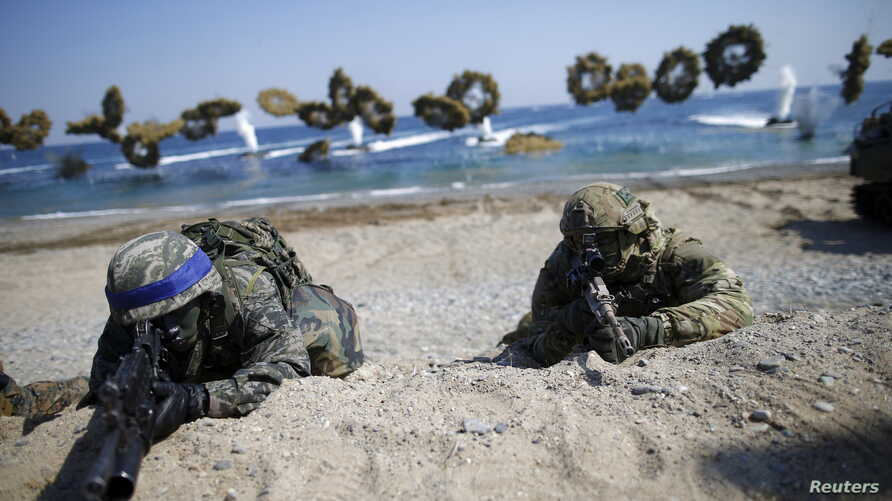 South Korean (blue headbands) and U.S. Marines take positions as amphibious assault vehicles of the South Korean Marine Corps fire smoke bombs during a U.S.-South Korea joint landing operation drill in Pohang, South Korea, March 12, 2016.