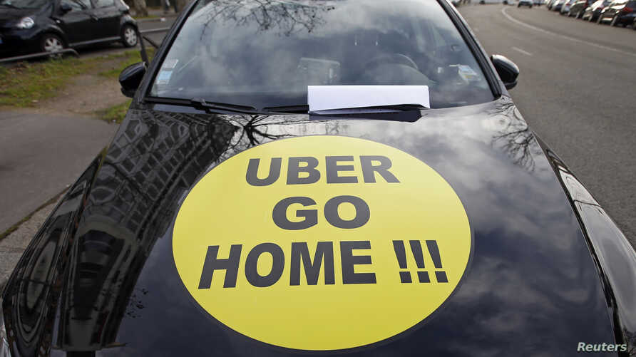 """A striking French taxi drivers displays the message, """"Uber Go Home"""" during a national protest about competition from private car ride firms like Uber, in Paris, Jan. 26, 2016."""