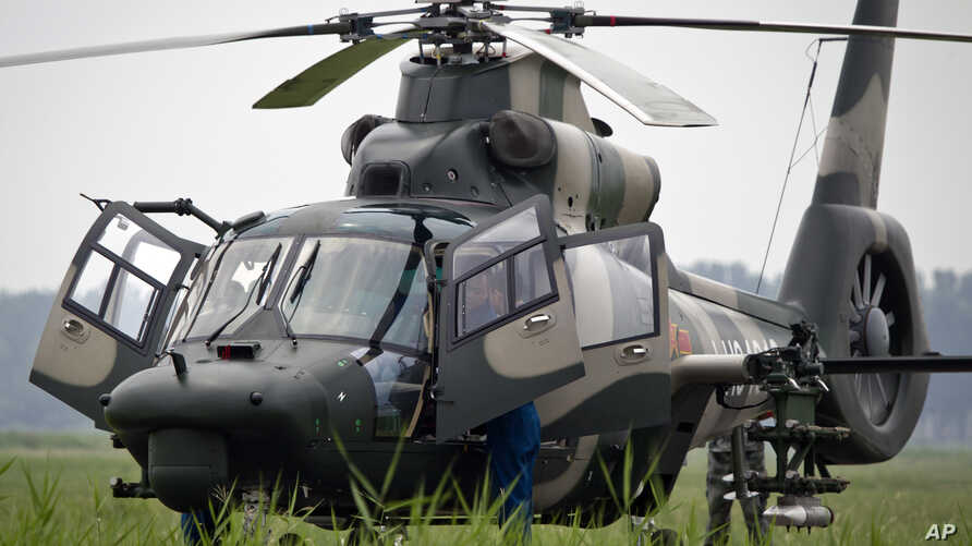 Flight crew of a Z-9WZ attack helicopter, designed and manufactured by China, chat after a flight demonstration for press at a Chinese Liberation Army base, ahead of Army Day on Aug. 1, on the outskirts of Beijing, China Tuesday, July 24, 2012.