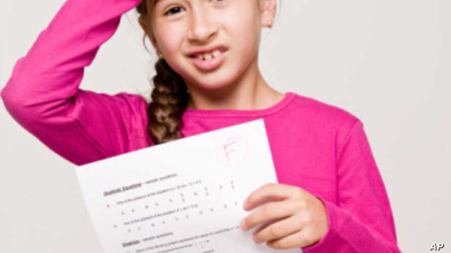 "A student holds a test with the failing letter grade of ""F"
