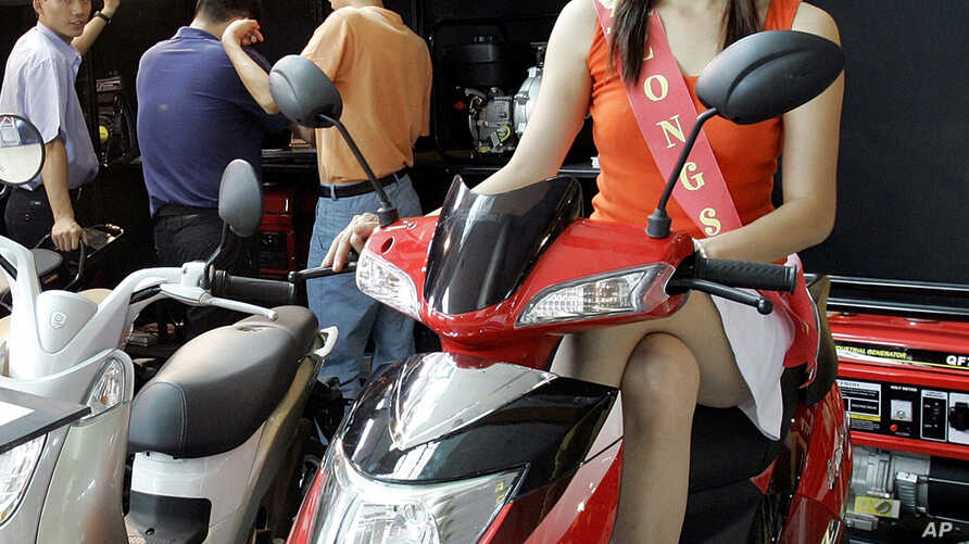 FILE - A model sits on a motor bike at a China-based Zongshen's booth during the Vietnam Auto Expo 2008 at Vietnam Exhibition & Fair Centre in Hanoi, Vietnam, June 11, 2008.