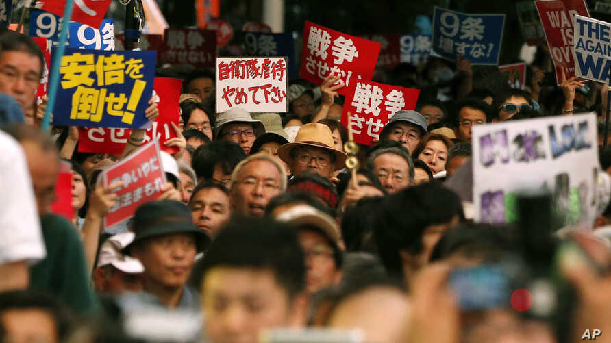 Protesters waving anti-war and anti-Shinzo Abe placards stage a rally in front of the Parliament building after a parliamentary committee approved legislation that would expand the role of Japan's military in Tokyo, July 15, 2015.