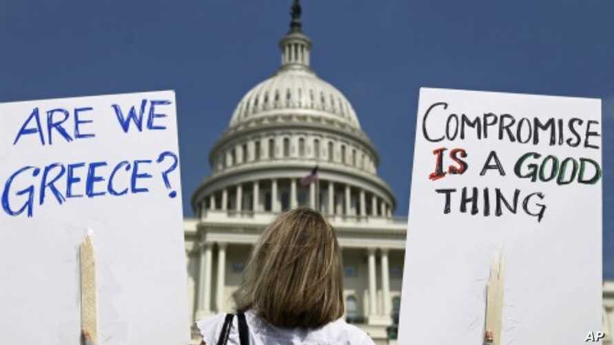 A demonstrator holds placards to protest U.S. debt in front of the US Capitol in Washington, July 18, 2011 (file photo).