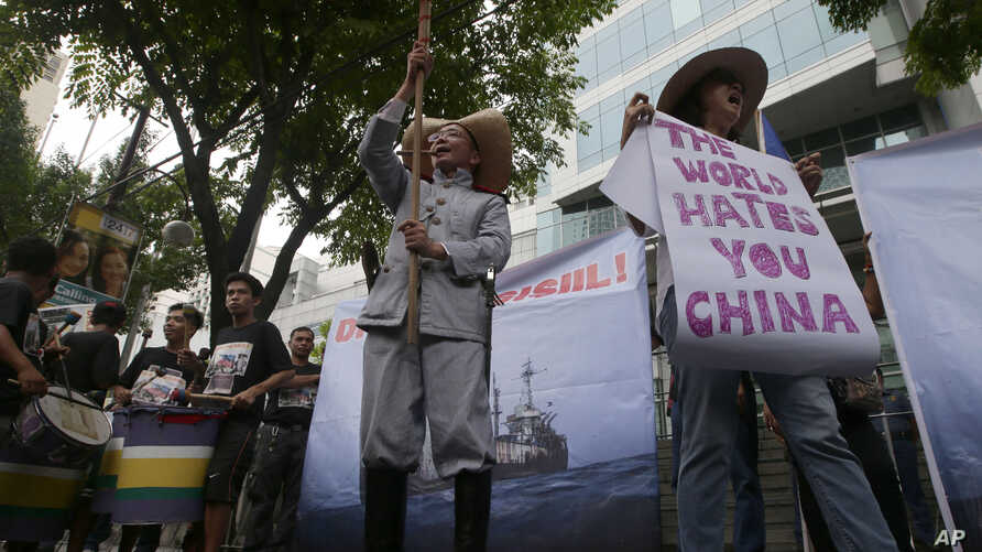 Protesters display placards while shouting slogans outside the Chinese Consulate in Manila against China's construction in a disputed are of the South China Sea, June 12, 2014.