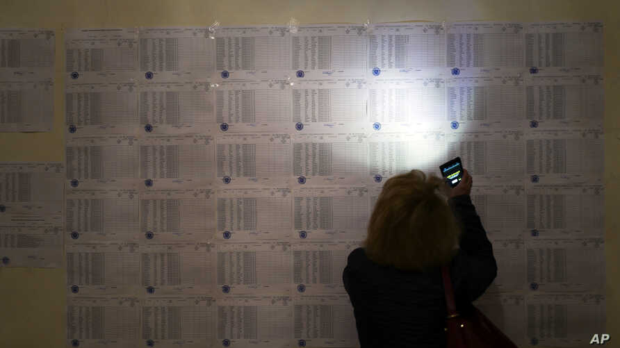 A woman uses the light of her cell phone to search for her name to vote, at a polling station during a parliamentary election in Yerevan, Armenia, April 2, 2017.