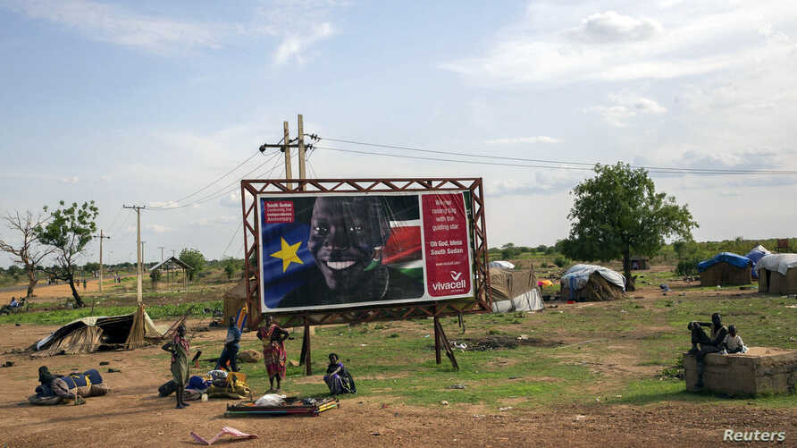 Civilians preparing to flee from renewed attacks gather in front of a sign celebrating the second anniversary of South Sudan's independence in Bentiu, Unity state of South Sudan, April 20, 2014.