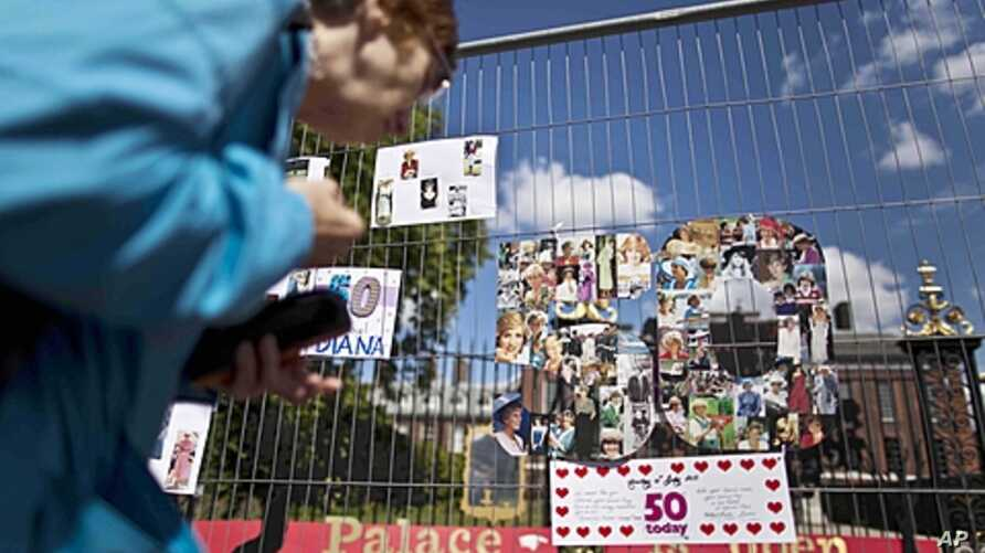 A woman looks at a montage of images of Princess Diana in the shape of a number fifty on fencing outside Kensington Palace in London, which was the residence of the princess, July 1, 2011.