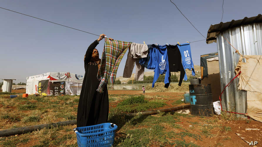 FILE - A Syrian refugee woman hangs laundry at a Syrian refugee camp in the eastern Lebanese town of Majdal Anjar, Lebanon, June 19, 2014.