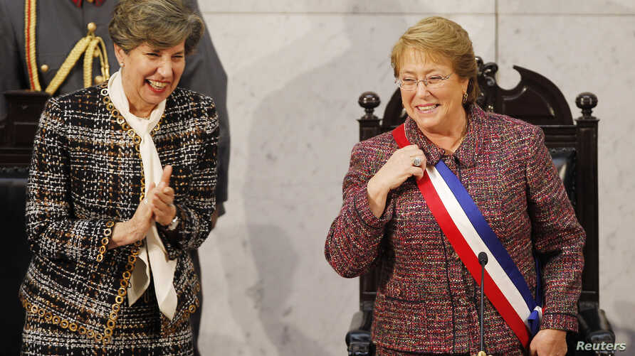 Chile's President Michelle Bachelet smiles next to Senate President Isabel Allende (L), daughter of late former President Salvador Allende, after delivering her annual address at the national congress building in Valparaiso city, northwest of Santiag...