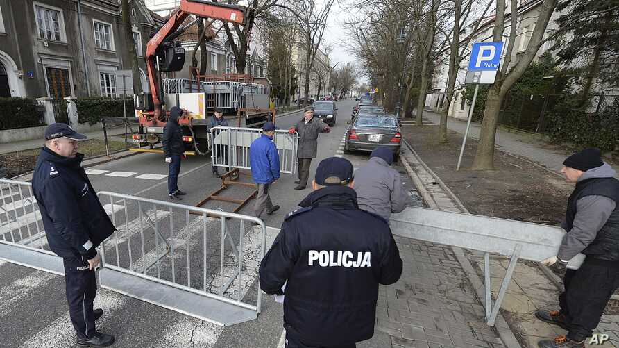 City workers put up barriers around the Israeli Embassy in Warsaw, Poland, Jan. 31, 2018, after a local governor, citing security concerns, banned traffic in the area in order to prevent a planned protest by far-right groups.