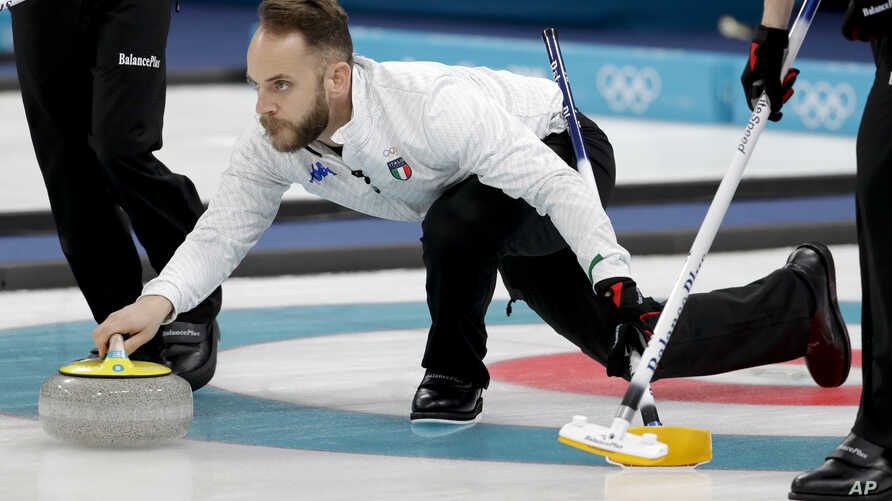 Italy's skip Joel Retornaz throws a stone during a men's curling match against Norway at the 2018 Winter Olympics in Gangneung, South Korea, Feb. 20, 2018.