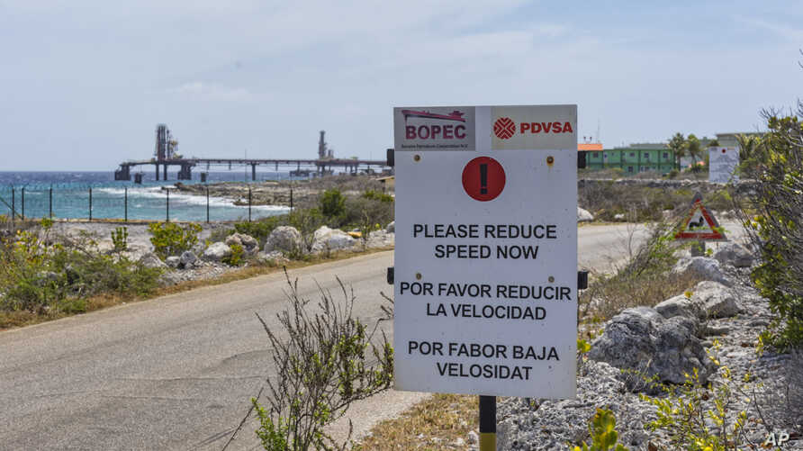 A warning sign stands at the entrance of the PDVSA/BOPEC Brasil Terminal in Rincon Bonaire on the Caribbean Netherlands island of Bonaire, May 7, 2018, where Venezuela refines and stores its heavy crude.