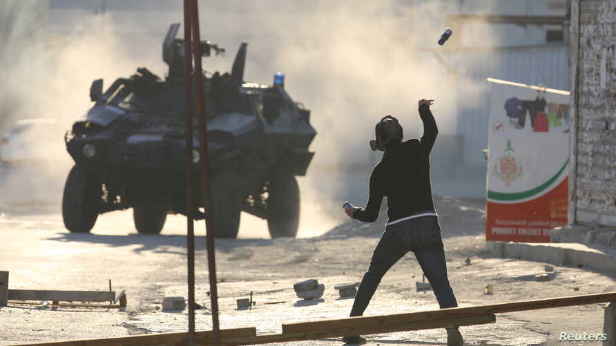 A protester throws a glass bottle containing paint at a riot police armoured personnel carrier during anti-government clashes in the village of Sitra, south of Manama, February 14, 2016.