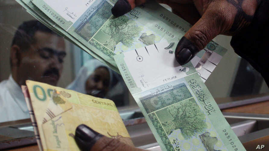 A woman displays Sudan's new currency at the central bank in Khartoum, Sudan, (File photo).