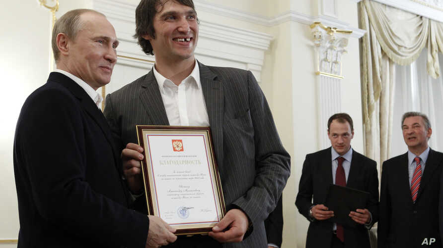 FILE - Russian national ice hockey team member Alexander Ovechkin, right, holds a certficate of recognition given to him by  President Vladimir Putin, left,  in the Novo-Ogaryovo residence outside Moscow, Tuesday, May 29, 2012.