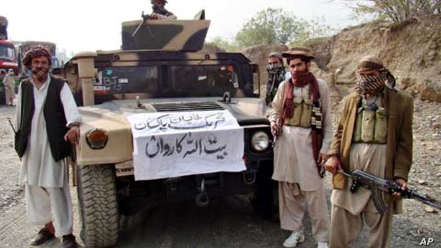 Armed militants of Tehreek-e-Taliban Pakistan (TTP) pose for photographs next to a captured armored vehicle in the Pakistan-Afghanistan border town of Landikotal on November 10, 2008, after they hijacked supply trucks bound for Afghanistan.