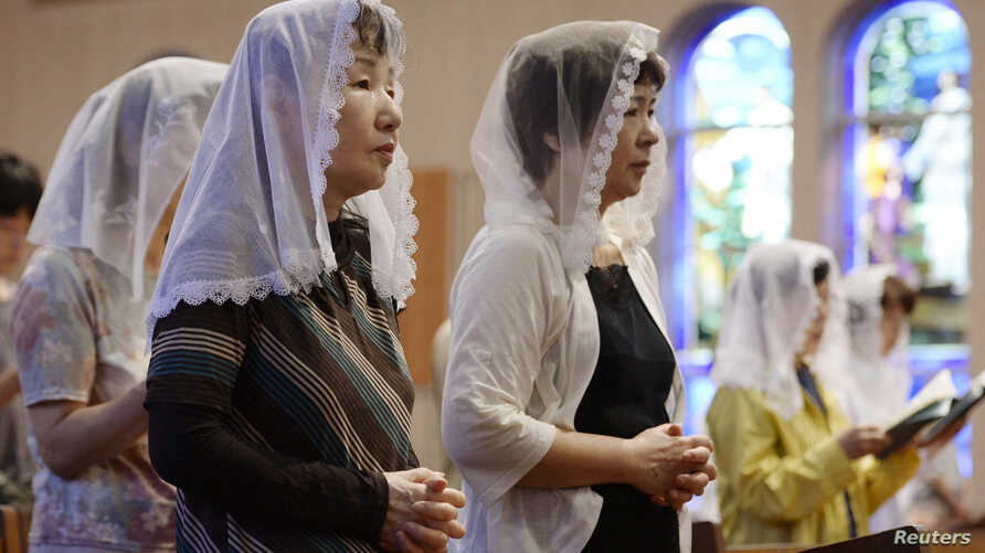 Local residents pray for victims of the 1945 atomic bombing during a mass at the Urakami Cathedral in Nagasaki, western Japan, on the 68th anniversary of the bombing of Nagasaki, in this photo taken by Kyodo, Aug. 9, 2013.